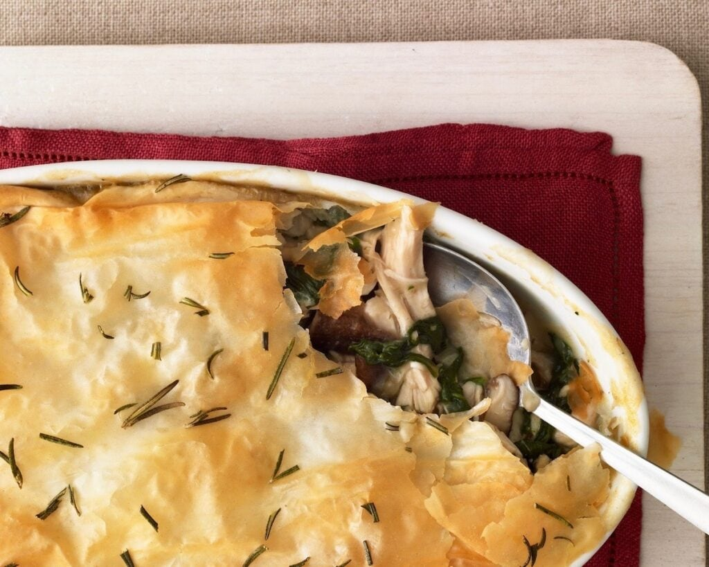 Chicken and Spinach Casserole with silver spoon scooping up a serving