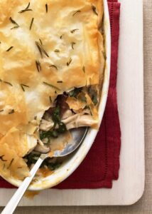 Chicken Spinach Mushroom Pie with serving spoon in white oval baking dish