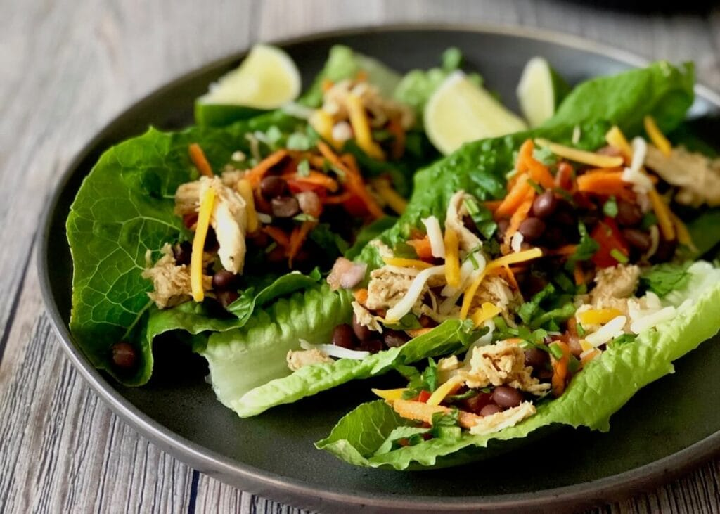 Healthy Taco Salad Lettuce Wraps on a plate with black beans chicken and slices of lime