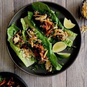 Overhead view of Healthy Taco Salad Lettuce Wraps on a plate with black beans chicken and slices of lime