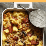 Onion Bacon Mushroom Strata in white baking dish with serving spoon