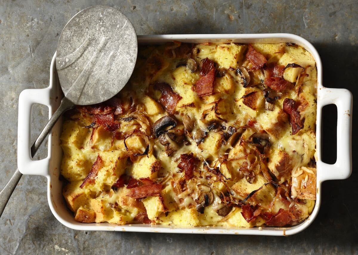 Baked Onion Bacon Mushroom Strata in white casserole dish with metal serving spoon