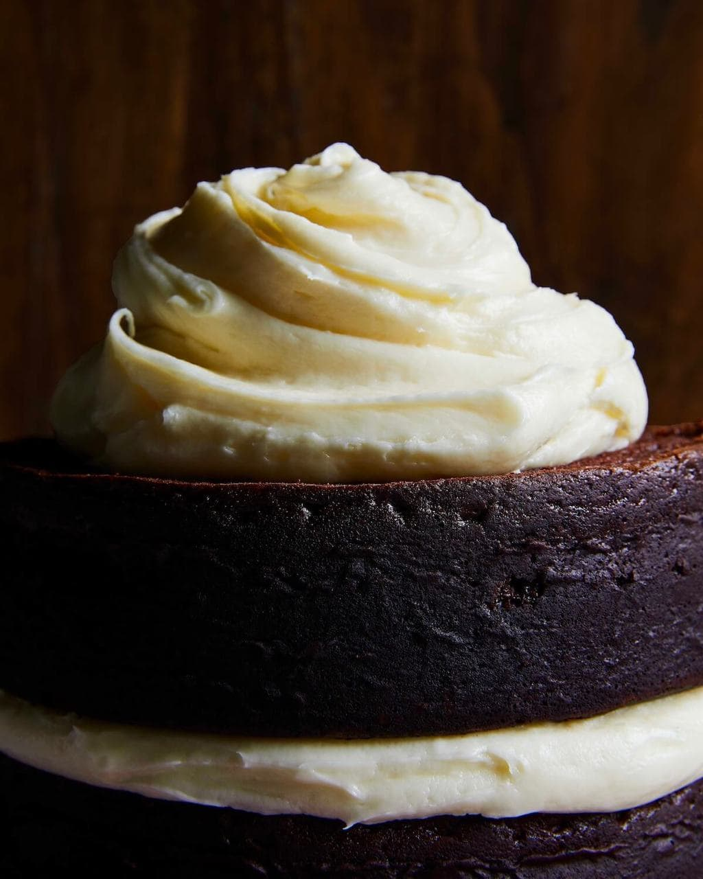 White cream cheese frosting on top of dark chocolate cake rounds
