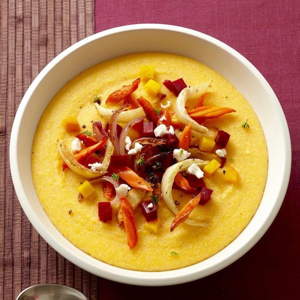 Creamy yellow polenta in a bowl topped with roasted vegetables