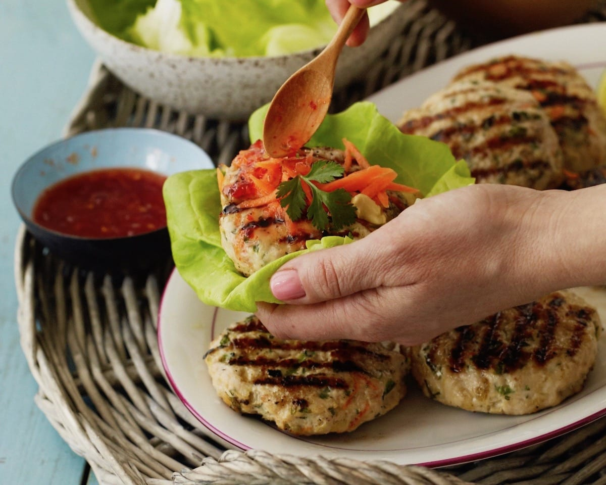 Thai Turkey Burger patties on white plate with lettuce sauce and shredded carrots