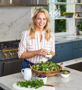 Tara in kitchen making salad