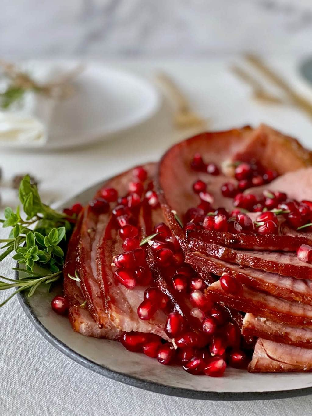 close up of cooked ham slices on platter with pomegranate and herbs