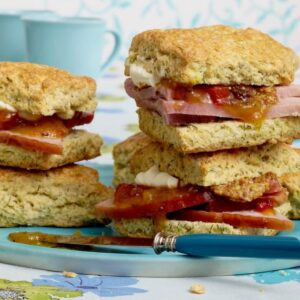 close up of biscuits with ham and chutney on blue plate