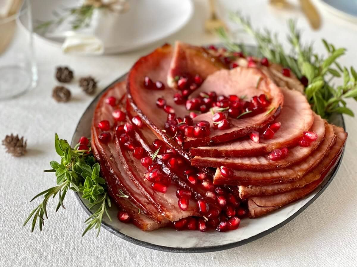 spiral cut ham with pomegranate arils on platter with herbs