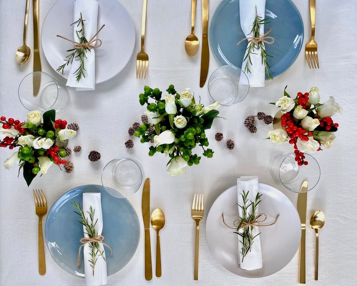 christmas dinner party table set up overhead on white linen