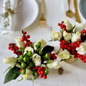 Christmas party ideas feature flowers in votives on white linen