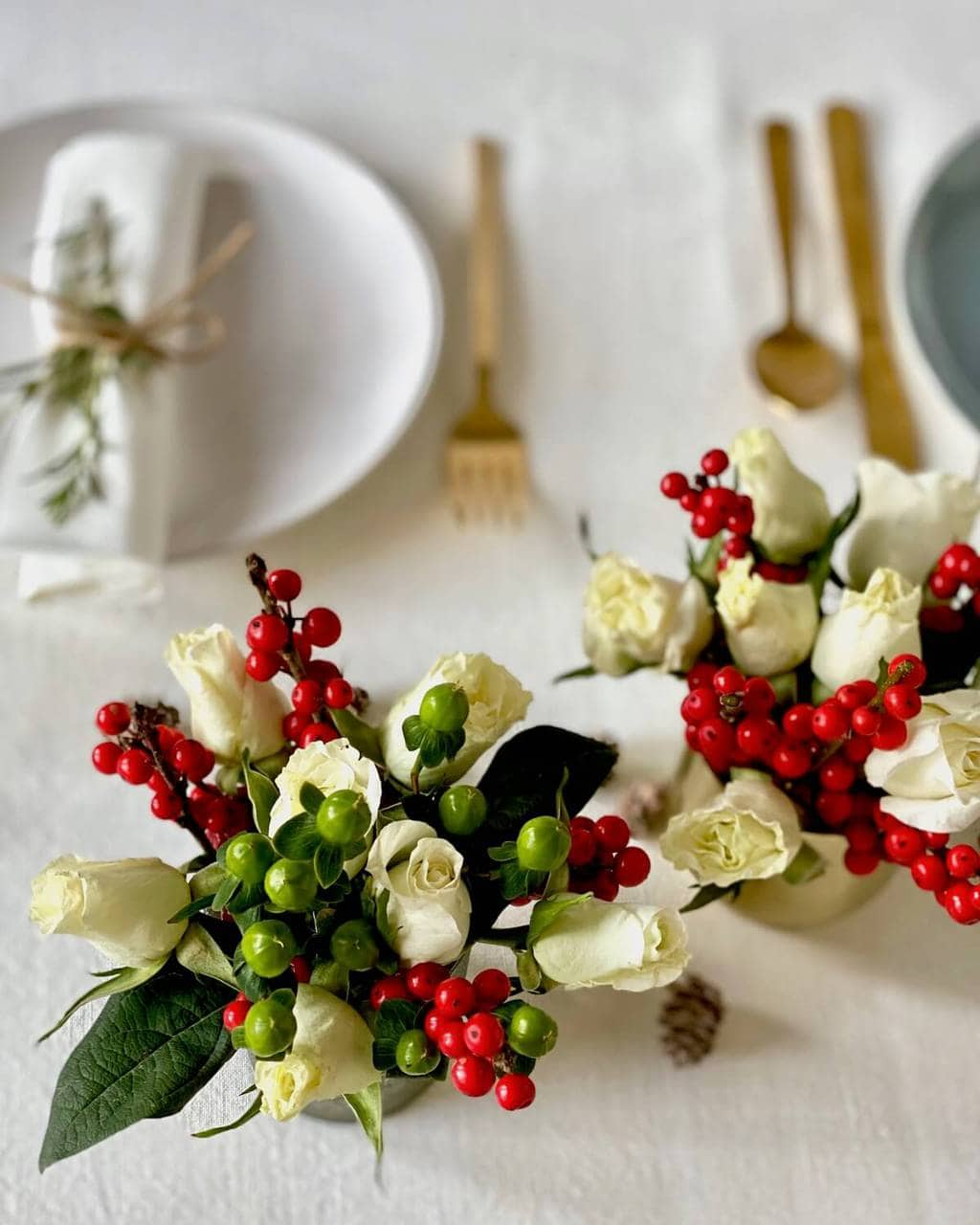 christmas table flower arrangement with roses and red berries