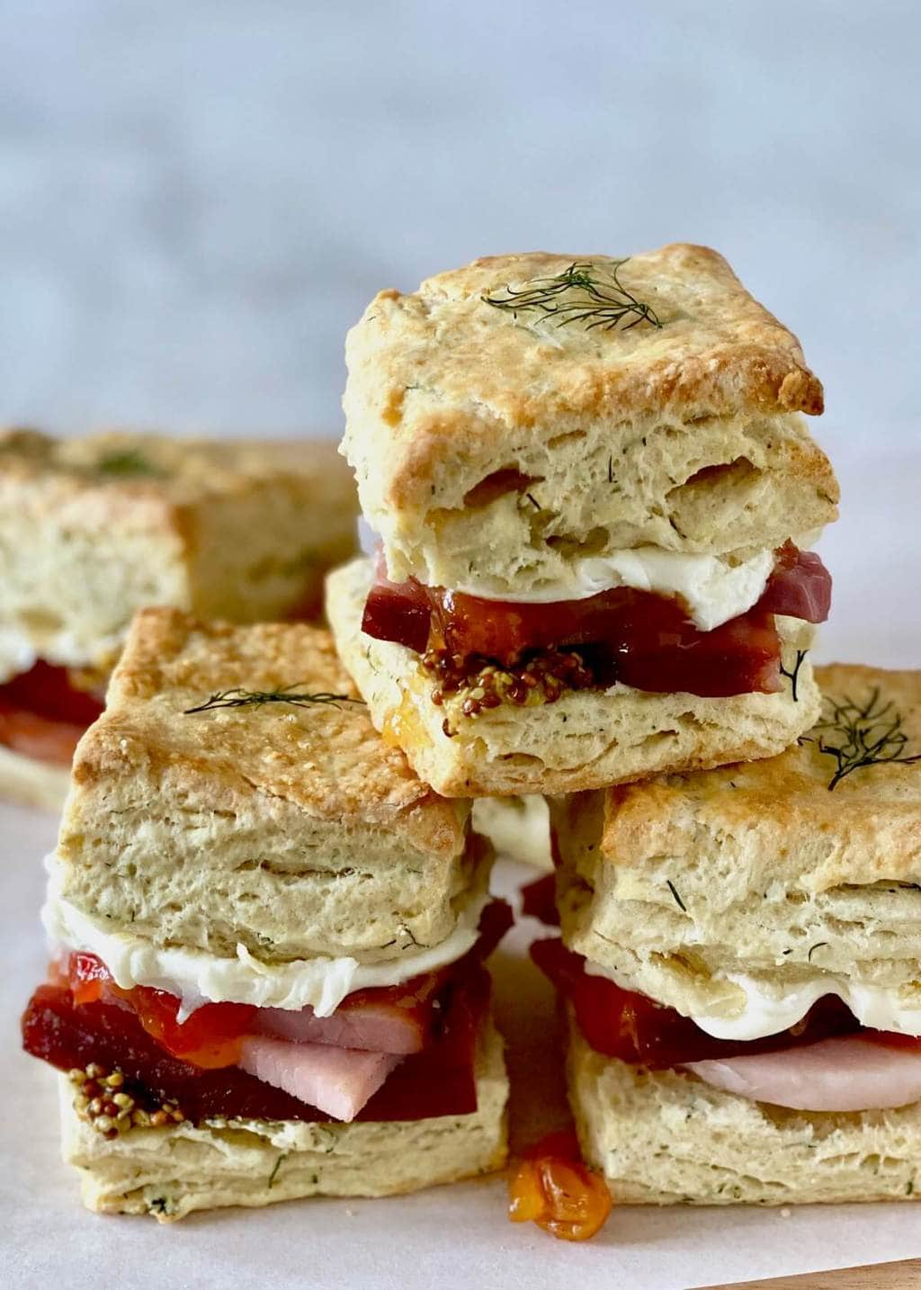 dill biscuits with ham and mustard on parchment