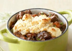 beef stew with biscuit top in green pan