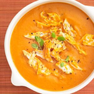 creamy tomato soup with chicken in a white bowl