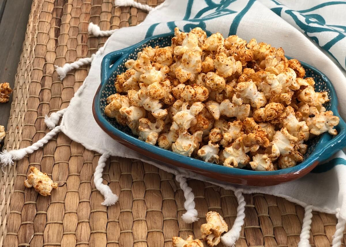 Sweet Chili Spiced Popcorn in blue bowl on brown woven placemat