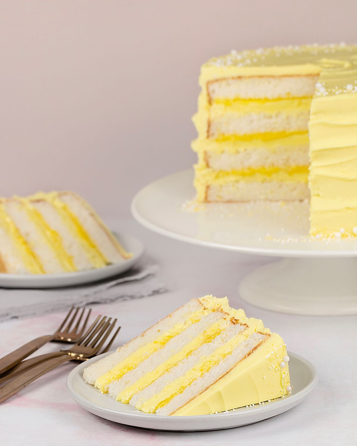 Lemon Cake on cake stand with two slices on plates