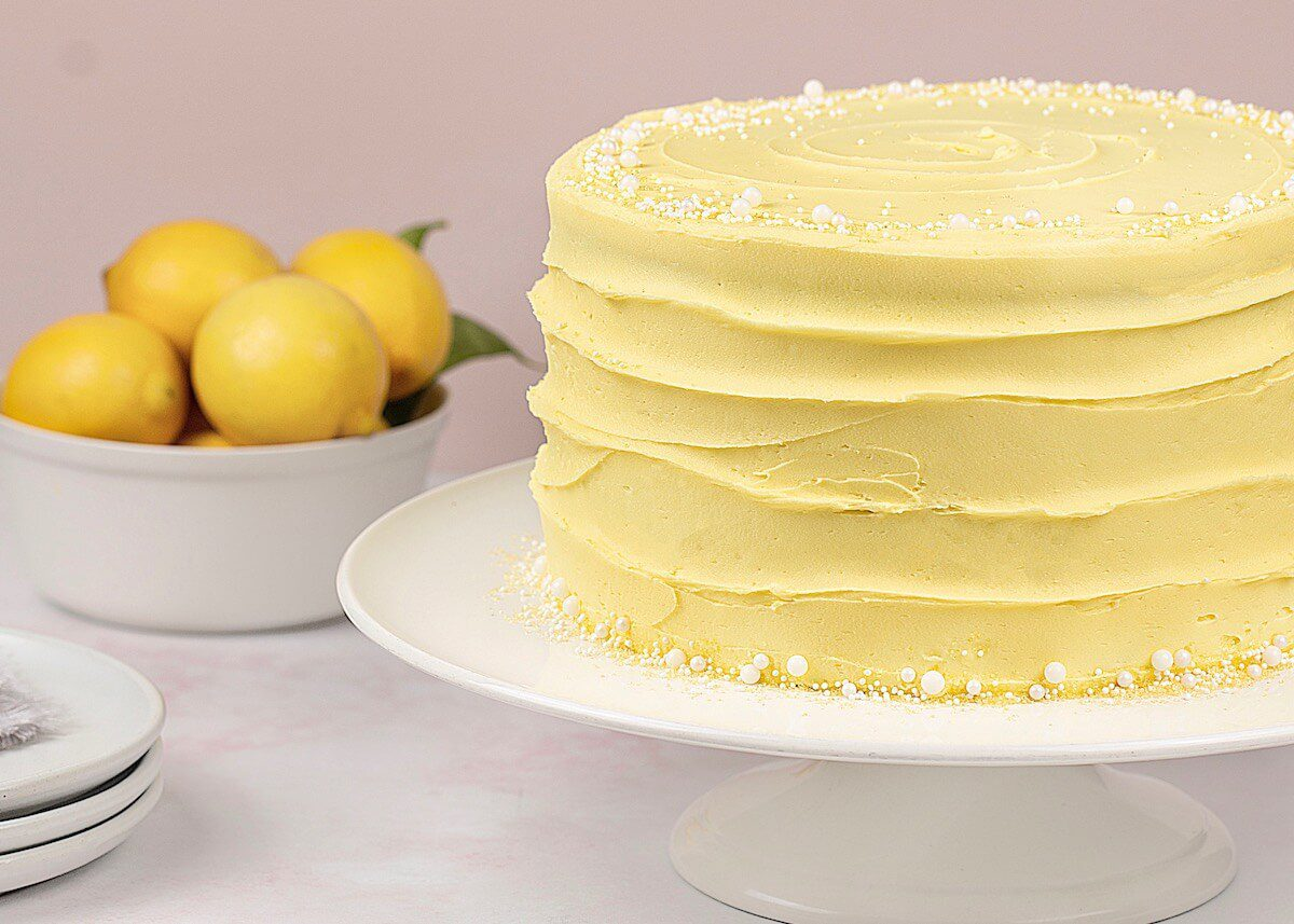 Lemon Cake on white cake stand with a bowl of fresh lemons in the background
