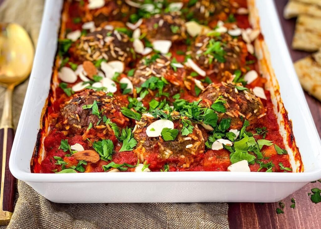 porcupine meatballs in white baking dish with parsley