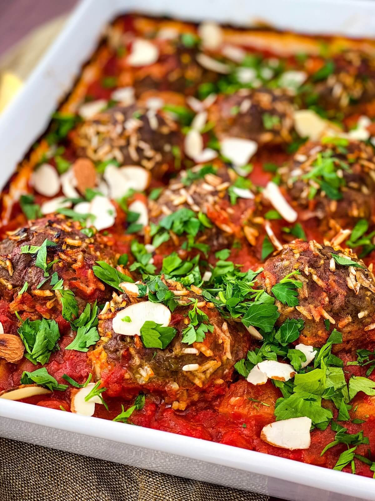 meatballs with parsley and almonds on top in a dish