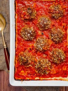 Beef Moroccan Porcupine Meatballs in white casserole dish with spoon