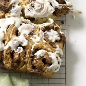 iced cinnamon rolls on a rack