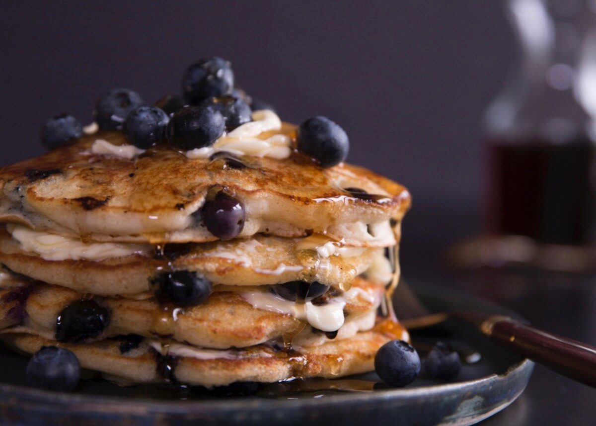stack of blueberry pancakes with butter and syrup