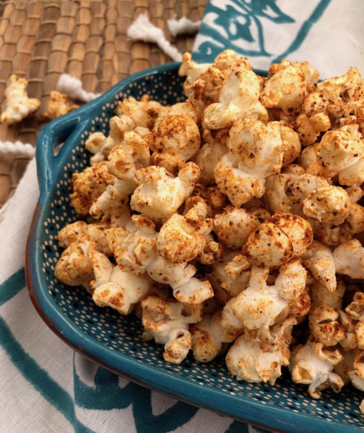 chili spiced popcorn in blue bowl with napkin