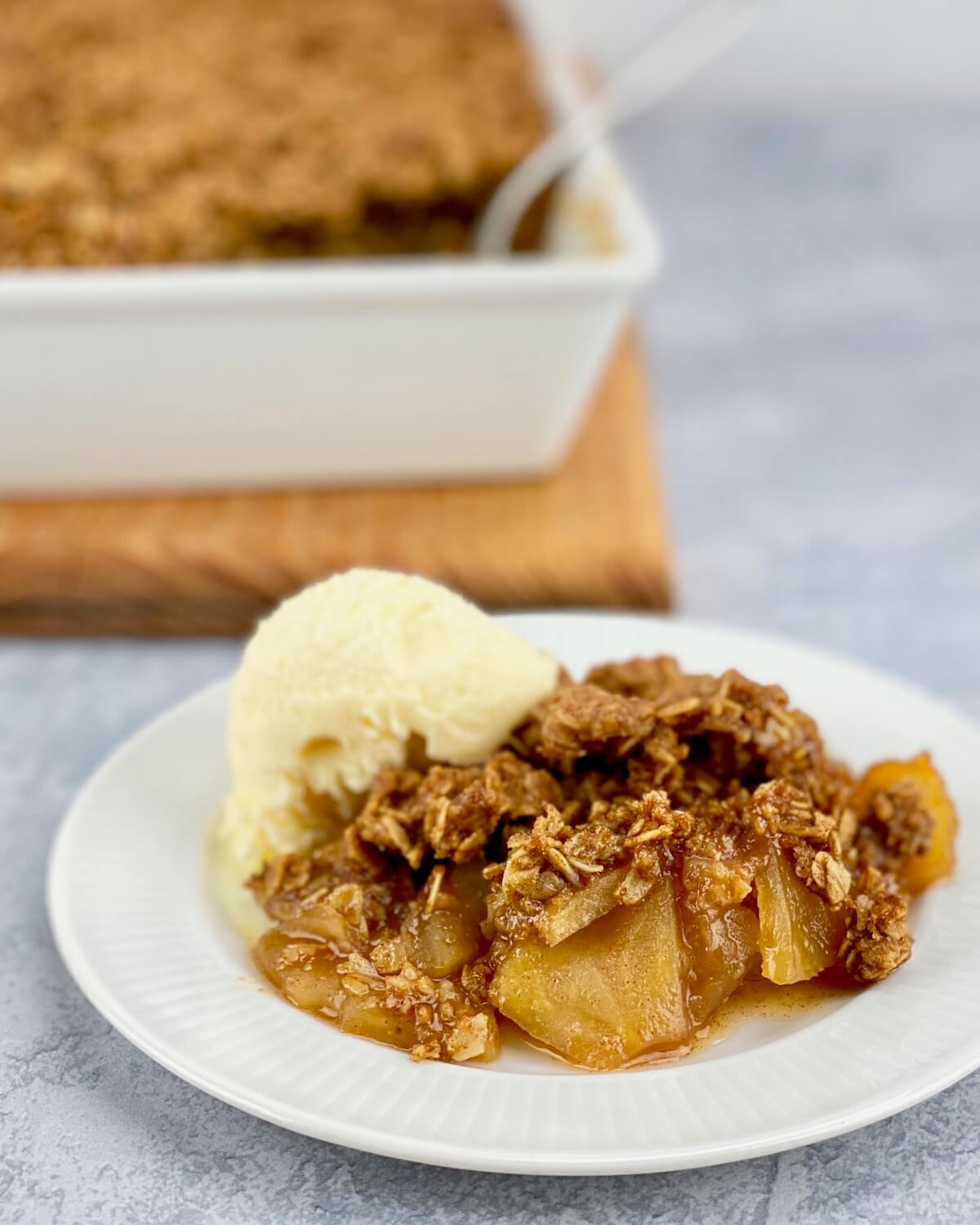 apple crisp with oats on small white plate with ice cream