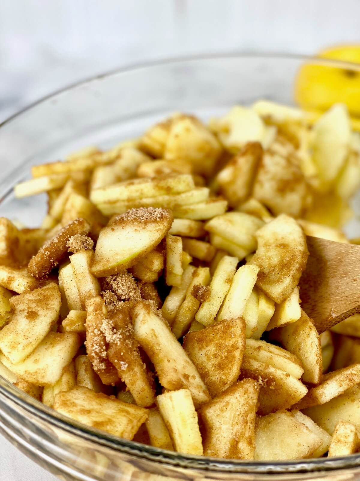 slice apples with brown sugar and cinnamon in medium-size glass bowl