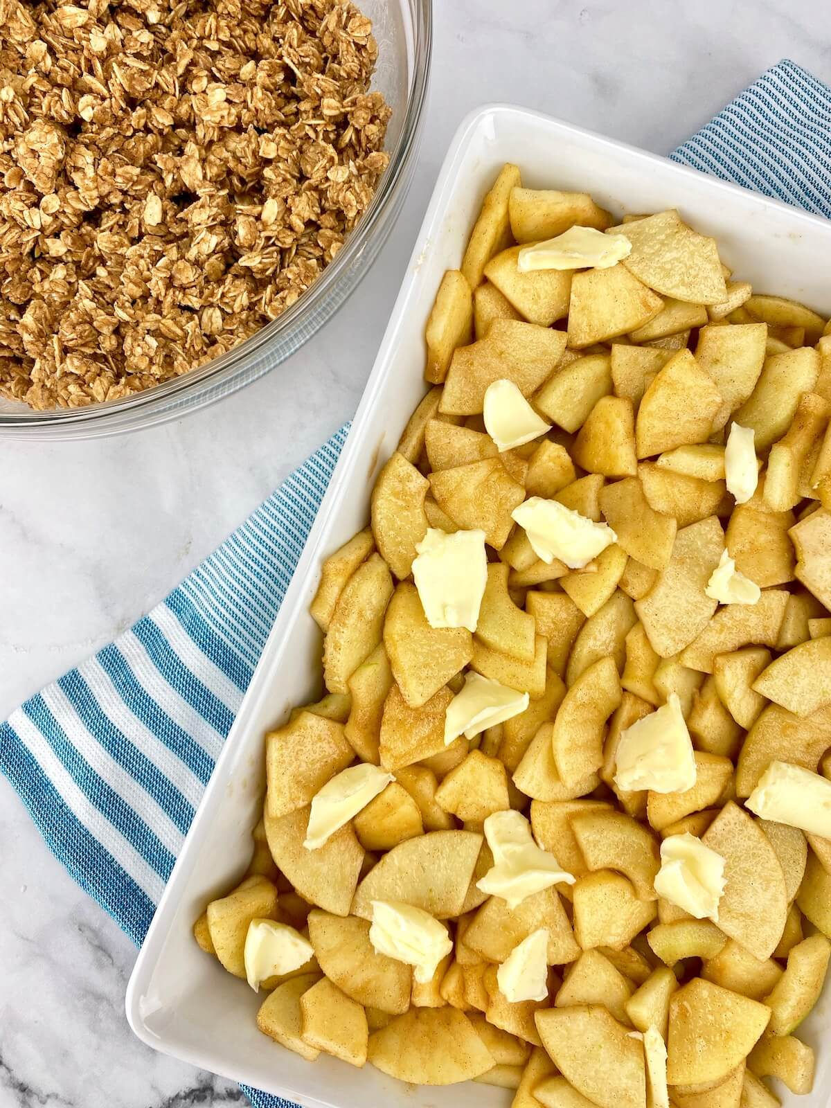 apples and butter in white 9 by 13 dish with oat topping to the side