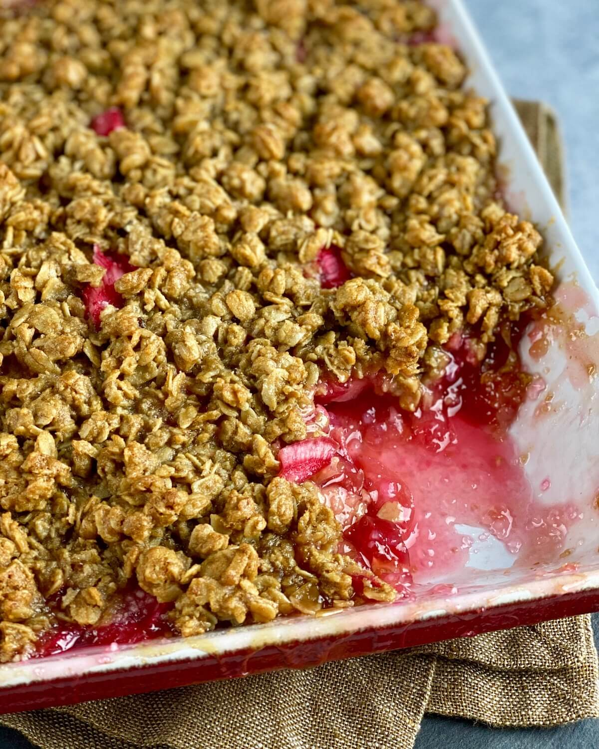 rhubarb with oat crisp scooped out of baking dish