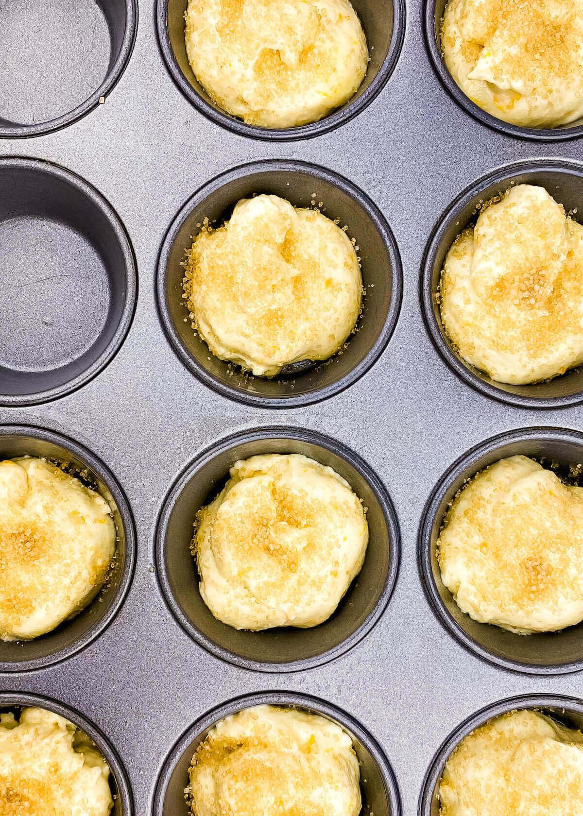 orange muffins in pan with sugar