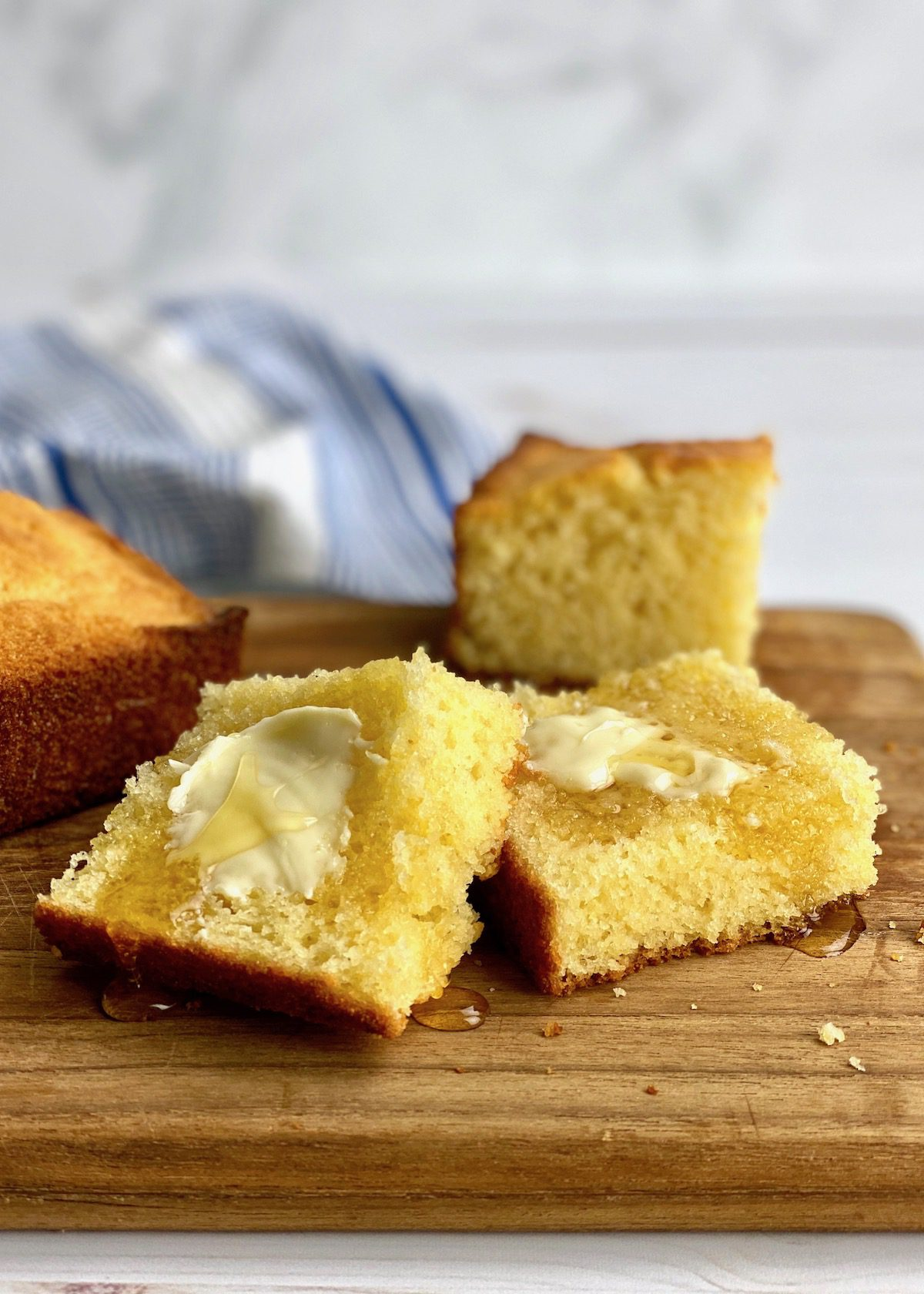 homemade cornbread with butter and honey on a board