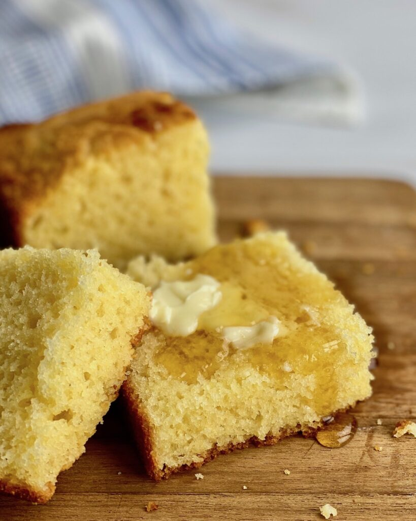 close up of cornbread with butter and honey