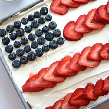 Cake with a flag decoration with blueberries as the stars and strawberries as the stripes.