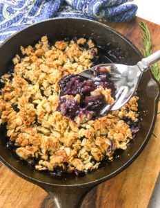blueberry crisp in a skillet with a spoonful taken out