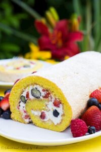 Roll Cake on a white platter with berries around it