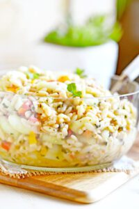 Garden Cucumber and Tomato Orzo Salad in a glass bowl on a cutting board