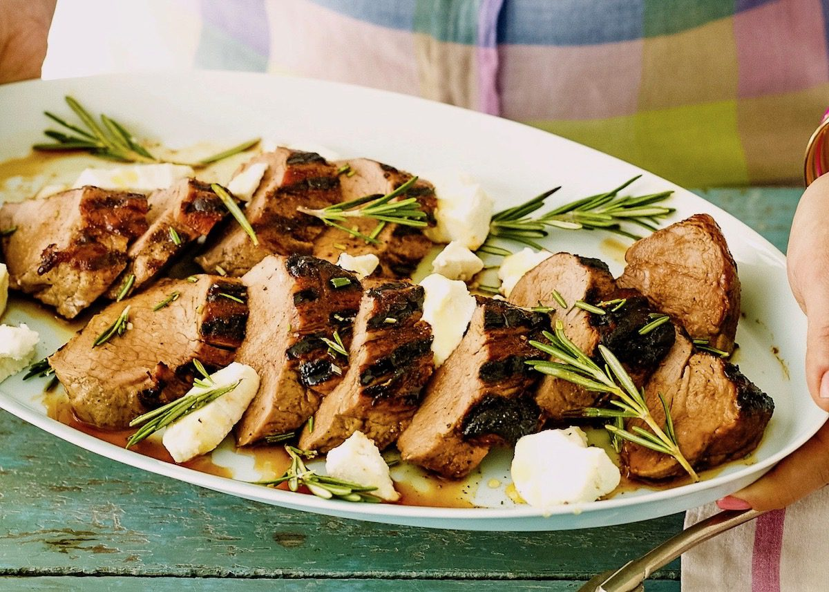 grilled pork tenderloin on oval white platter with rosemary