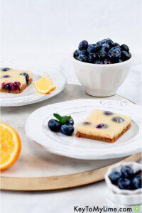 Lemon-blueberry bars on a circle cutting board