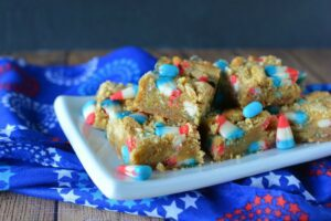 Cookie Bars cut up o na white plate with a patriotic napkin underneath.