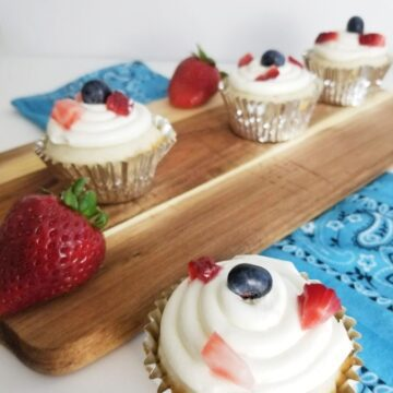 Cupcakes in foreground and on a cutting board with strawberries around it.