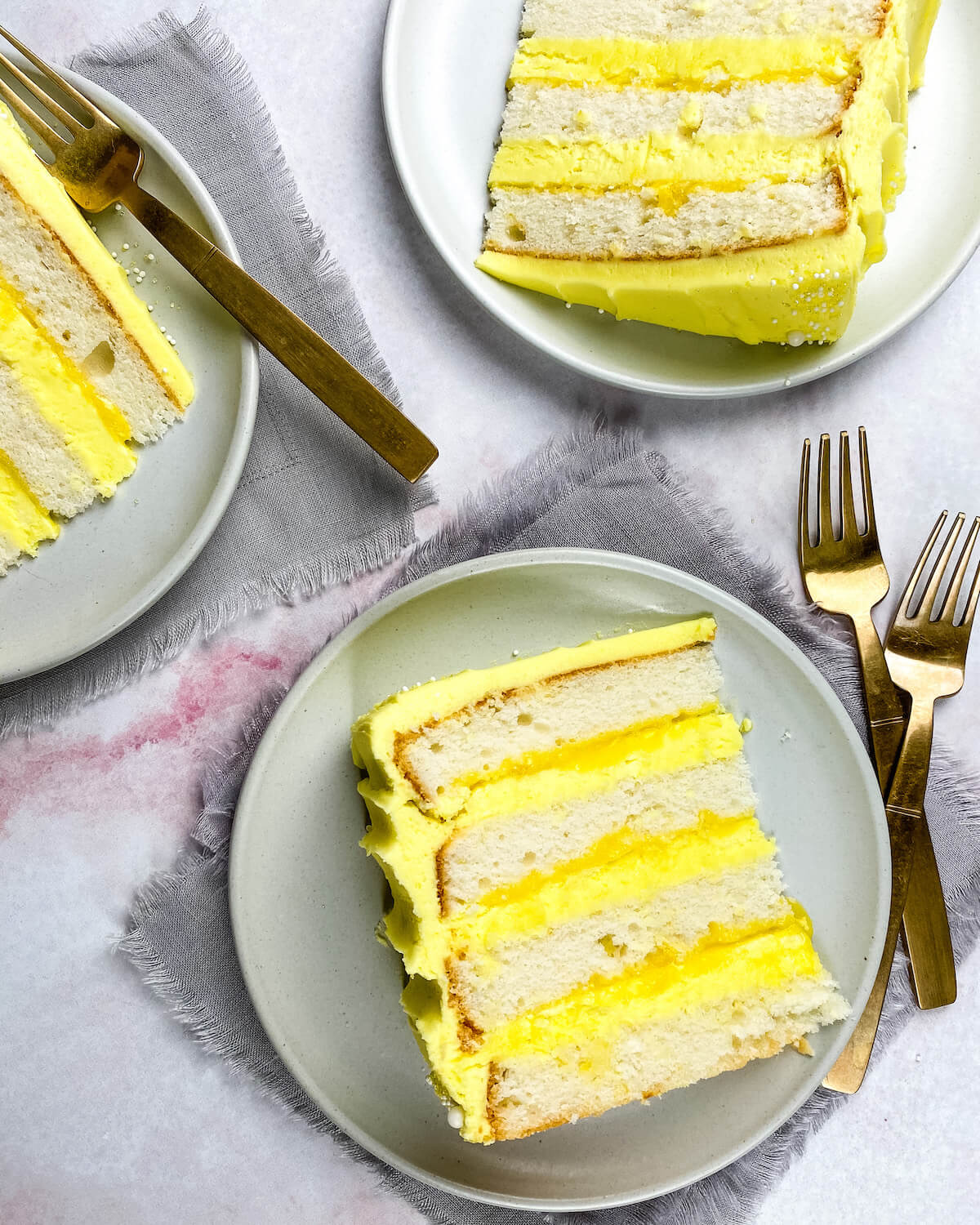 white cake with lemon curd and frosting sliced on plates