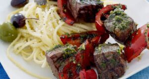 close up of beef kabobs with pesto for social media