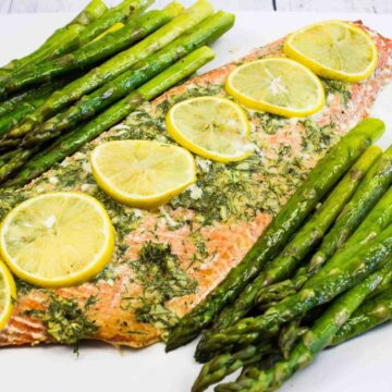 Salmon with asparagus on white platter