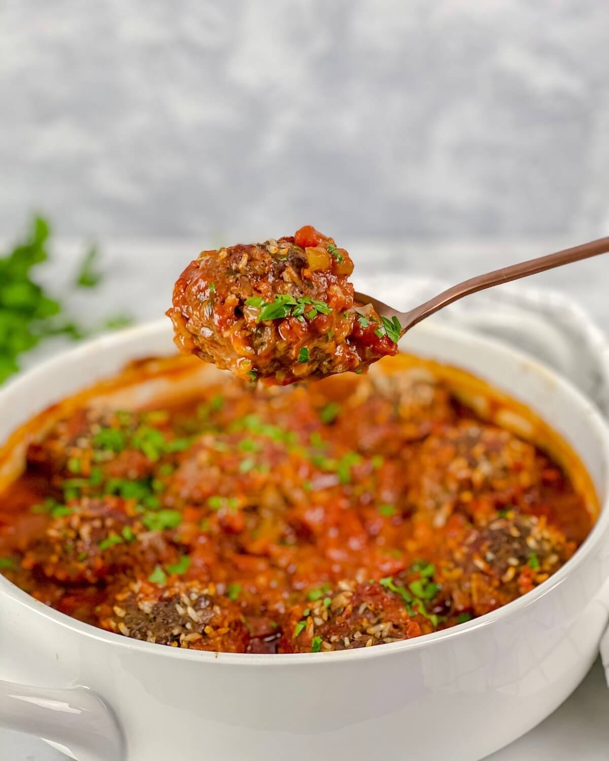 spoon with beef meatball on it with tomato sauce