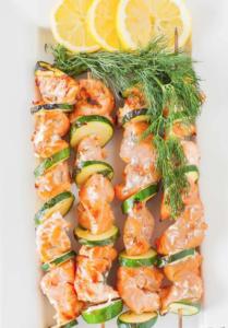 salmon kabob next to each other lemon on top