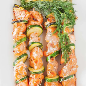 salmon kabob next to each other lemon on top
