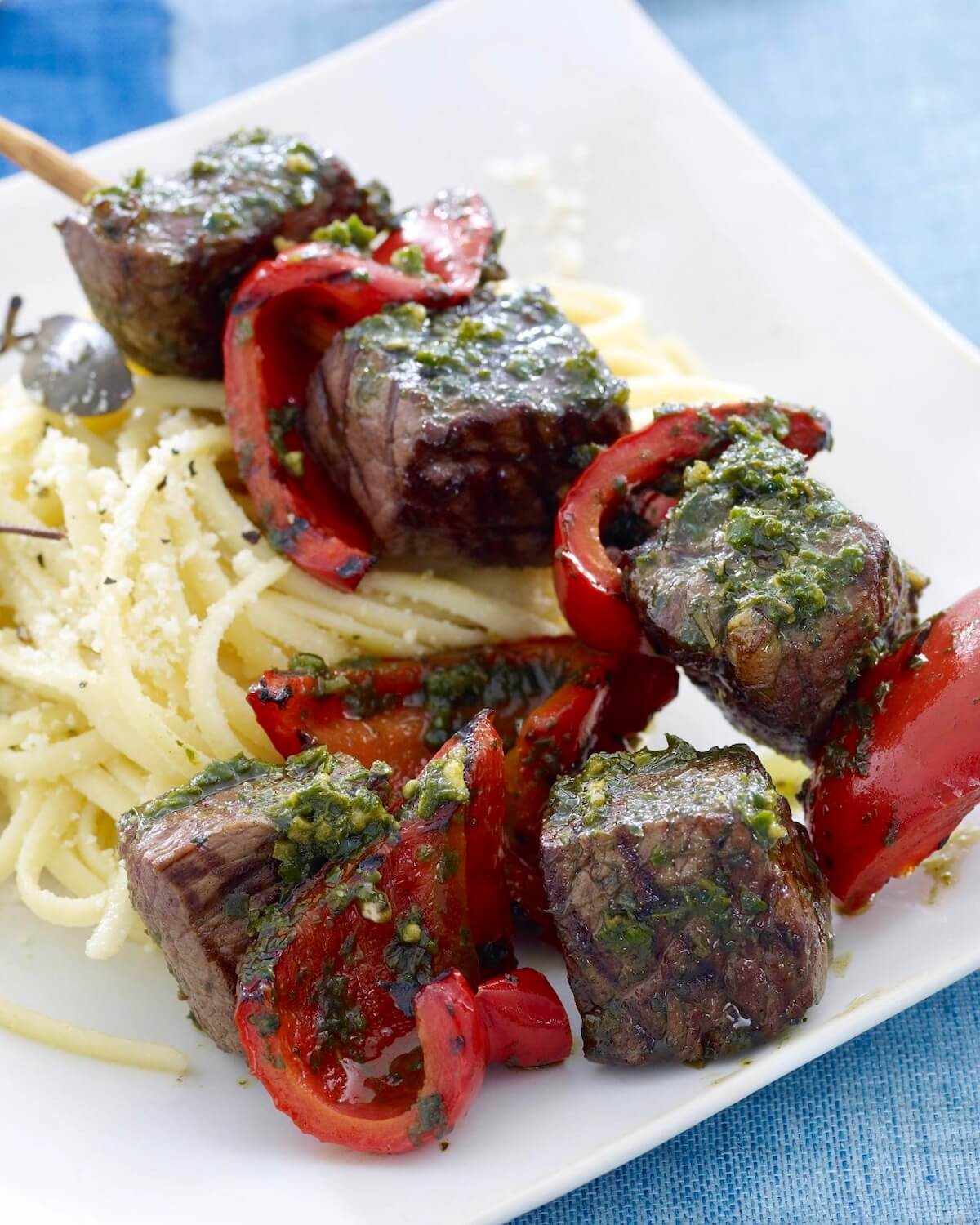 grilled beef kabobs with peppers and pasta on white plate